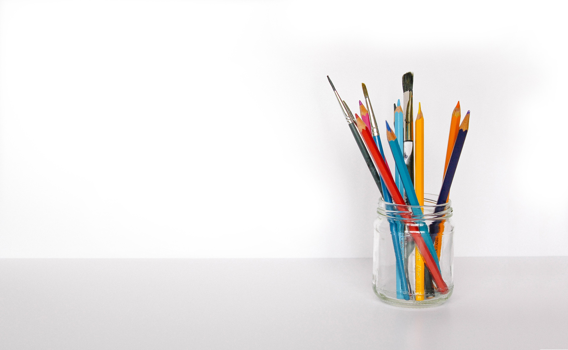 Colouring pencils and paint brushes in a glass jar