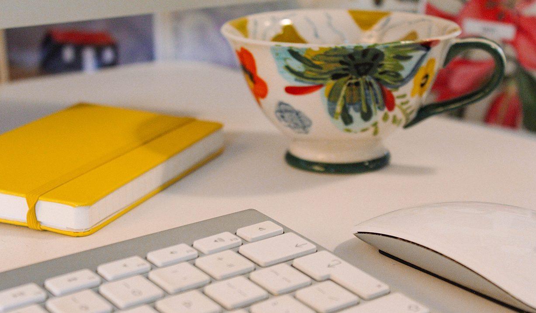 Desk with keyboard, notebook & floral teacup