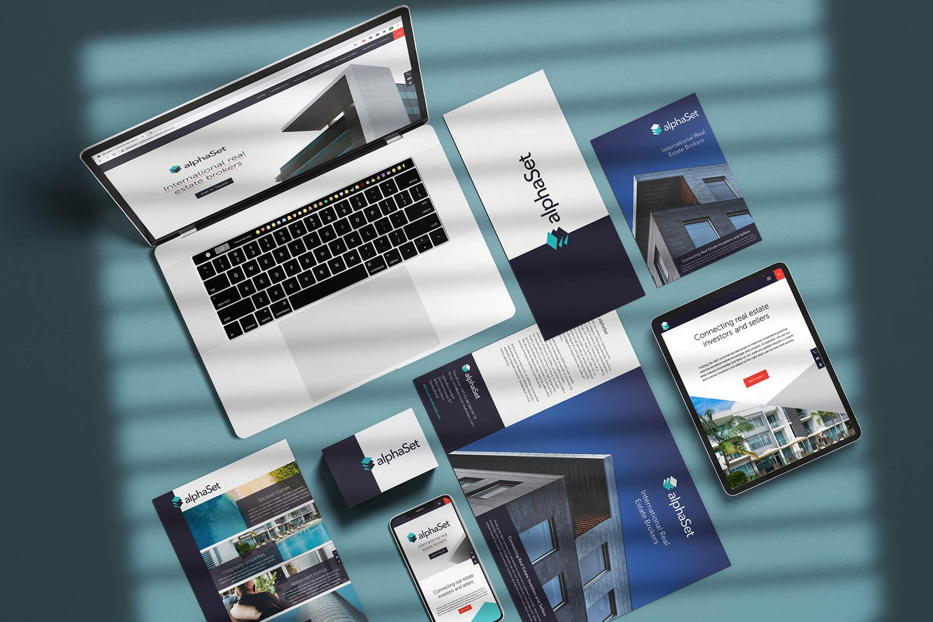 Sample of alphaSet client work on laptop and brochures